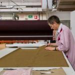 La salariée pique le tissu pour aligner les carreaux du motif